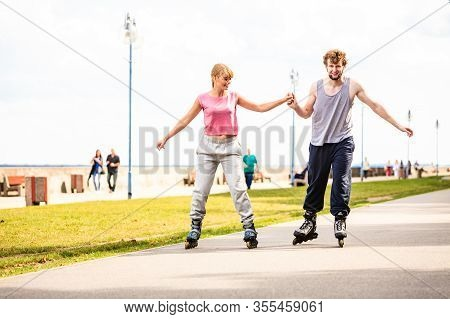 Active Young People Friends In Training Suit Rollerskating Outdoor. Woman And Man Couple Holding Han