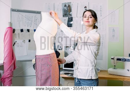 Young Female Stylist Measuring Pants On Mannequin With Tape. Woman Fashion Designer Working In Studi