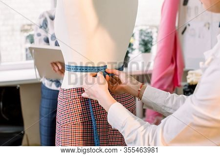 Design Studio. Pants On Mannequin And Measurement Tape In Woman Hands. Dressmaker Taking Dummy, Mann