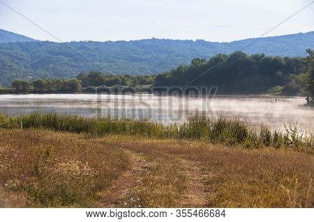Coastal Summer Landscape. Foggy Lake In Crimean Mountains At Sunny Summer Morning Under Cloudy Sky
