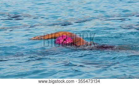 A Female Swimmer In An Outdoor Pool Freestyle Swiming Wearing A Pink Bathing Cap Face Down In The Wa