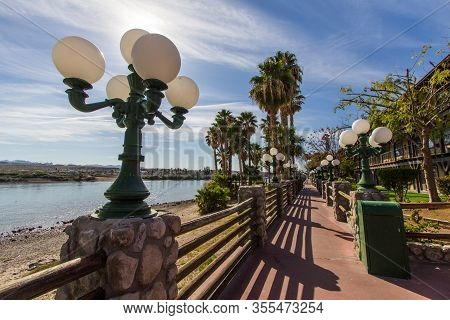 Riverwalk In Laughlin Nevada. Streetlights And Palm Trees Line The Empty  Riverwalk Along The Colora