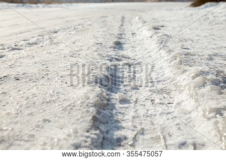 Track From A Wheel On An Icy Track. Dangerous Driving Conditions. Icy Road With Tracks From The Whee