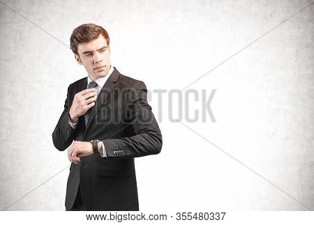 Portrait Of Confident Young European Businessman In Elegant Suit Checking His Wristwatch And Adjusti