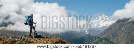 Young Hiker Backpacker Woman Using Trekking Poles Enjoying The Nuptse 7861m Mountain During High Alt