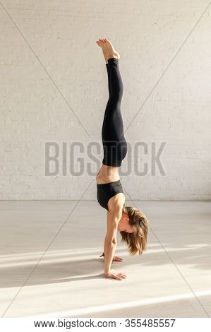 Athletic Girl With Barefoot Doing Handstand In Yoga Studio
