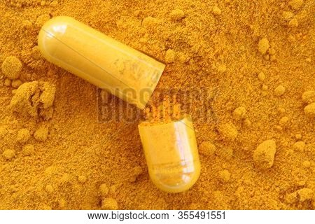 Turmeric Background With Curcumin Capsule Open Against Background.