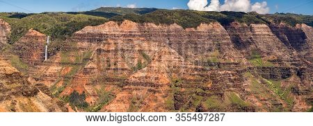 Broad Panorama Of The Red Rocks Of Waimea Canyon From The Waipoo Falls Overlook On Kauai In Hawaii