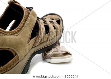 adult shoe stepping on baby sandal isolated on white background poster