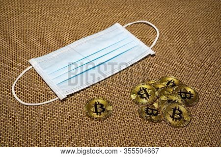 Gold Bitcoin Coins With A Medical Mask. A Business Finance Concept
