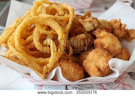 Simple Basket With Paper Napkin Filled With Fresh Fried Whole Belly Clams And Paper-thin Onion Rings