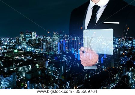 Businessman Investor Holding Digital Mobile Tablet With Graphic Candle Stick Graph Chart Of Stock Ma