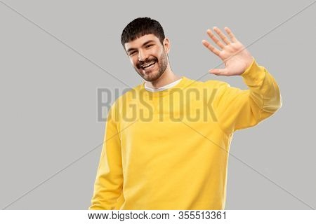 gesture and people concept - smiling young man in yellow sweatshirt waving hand over grey background