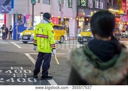 Taipei, Taiwan - January 08, 2020: Traffic Warden Controls And Monitors Traffic In Taipei After Dark