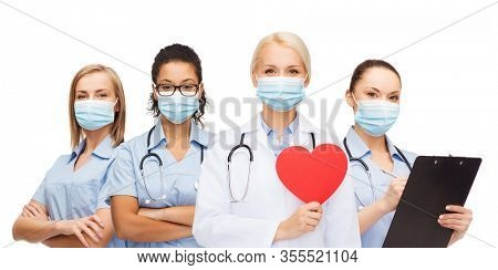 medicine, cardiology and healthcare concept - group of female doctors wearing protective medical masks with red heart and stethoscopes over white background