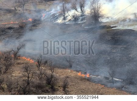 White Smoke From An Extinguished Fire In A Burnt Meadow. A Field With Burnt Grass. Fading Tongues Of