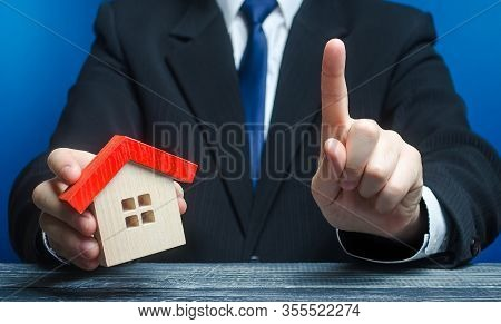 Man With A House Makes A Gesture Of Attention. Legal Advice On Terms A Contract Deal For Purchase Of