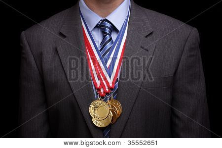 Gold medals hanging around a businessman neck concept for success and winning