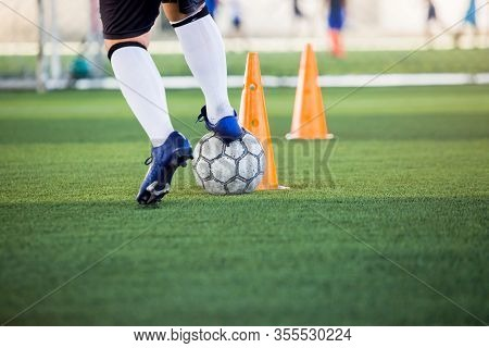 Soccer Player Jogging And Control Ball Around Cone Markers For Soccer Training. Football Academy.