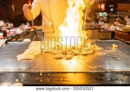 Teppanyaki Chef Cooking Japanese Seafood And Shrimp On Hot Metal Plate With Flaming Fire.