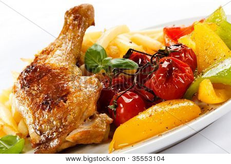 Grilled chicken leg, French fries and vegetables