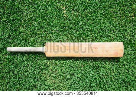 A Willow Cricket Bat On Green Grass.