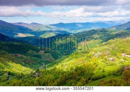 Rural Landscape In Mountains. Dappeled Light On Forested Hills. Beautiful Nature Scenery In Spring.
