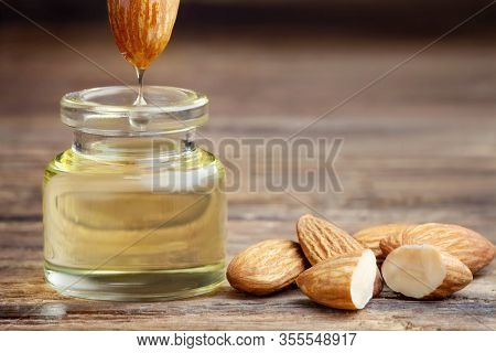 Almond Oil In Bottle And Nuts On Wooden Table