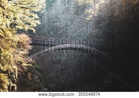 Rays Of Sunlight Cast Across The Wooden Bridge At Moulton Falls In Battle Ground, Washington, Usa.