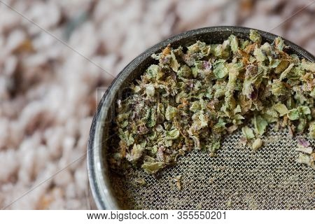 Ground Pieces Of Cannabis Flower Sit In A Metal Grinder. Cannabis Has Purple And Green Colors.