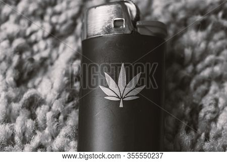 Black & White Photo Of Lighter With Cannabis Leaf Or Marijuana Leaf Shape On It. Lighter Laying On C