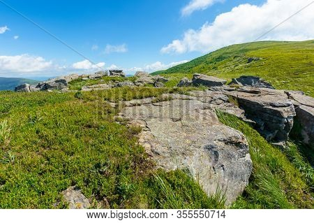 Rocks On The Alpine Hillside Meadow. Great Summer Nature Scenery. Green Grass On The Hills And Fluff