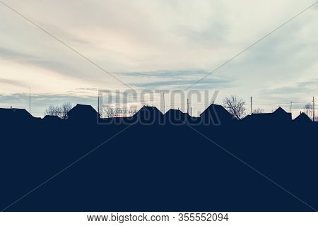 The Silhouette Of Houses And Roofs Against The Dawn. Rural Houses And Trees Against The Background O