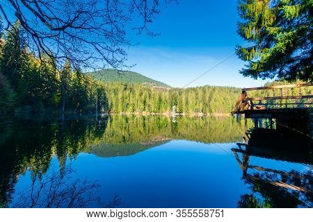 Mountain Lake Among The Coniferous Forest. Morning Nature Scenery With Pier Above Reflections In Cal
