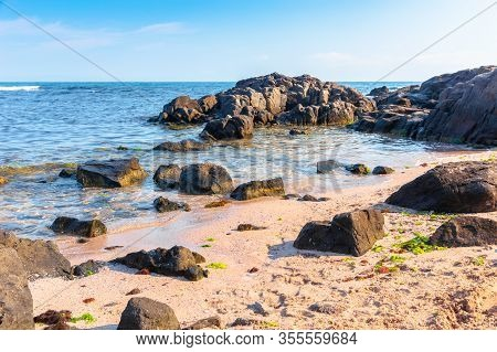 Rocks On The Sea Beach In The Morning. Calm Sunny Weather. Secluded Place. Fluffy Clouds Above The H