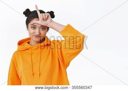 You Lost. Silly And Cute Young Asian Girl Scolding Friend For Losing, Making Loser Gesture With L Le