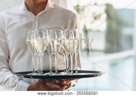 The Waiter Is Holding A Tray With Glasses Of Champagne Or White Sparkling Wine. Service In The Resta