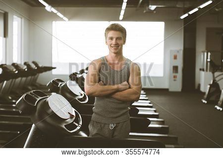 Young Man In Sportswear Smiling And Standing Near The Treadmill Before Or After Training On Gym. Car
