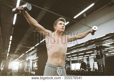 Portrait Of Athletic Man Exercising With Dumbbells In Gym. Athlete Man Exercises With Training Dumbb