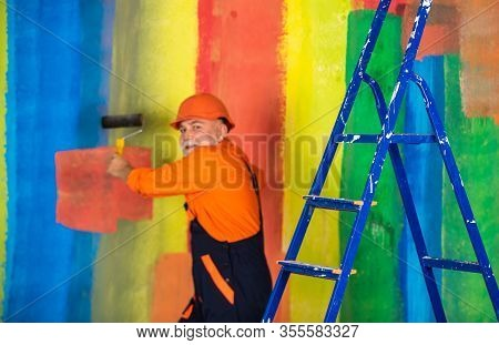 Senior Man Painter Use Roller On Ladder. Painting The Wall Colorful. Professional Painter In Working