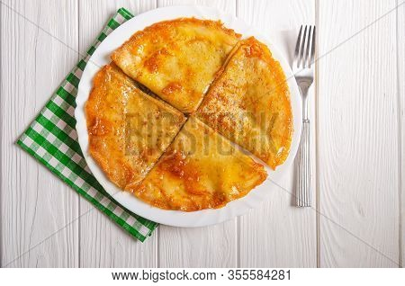 Crepe Suzette - Pancakes With Orange Syrup And Zest On A White Wooden Table. Homemade Pancakes With