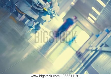 Fragment Of The Hospital Corridor With A Silhouette Of A Worker, The Patient's Bed And The Reflectio