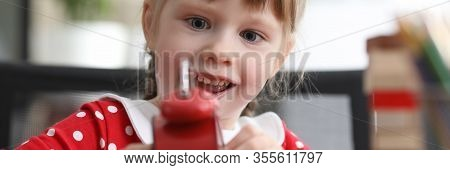 Portrait Of Involved Little Girl Playing With Alarm-clock. Cheerful Child Setting Time On Alarm. Smi