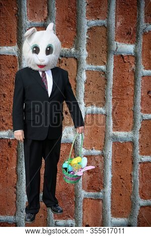 Easter Bunny. Easter Bunny in a Business Suit. Easter Bunny with a Red Brick Wall Background. Easter Bunny Man in a suit brings a basket of goodies for Holiday Fun to all. Man with a Rabbit Head.
