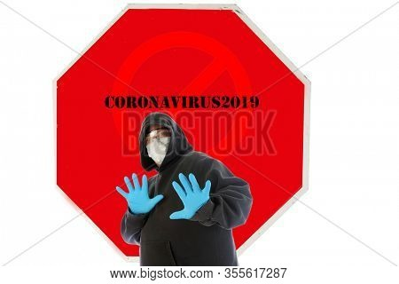 Stop Sign. Stop Coronavirus19. A man wearing a Hooded Sweat Shirt and Gloves and Mask holds his hand out in a STOP Symbol. Stop the COVID-19 Pandemic. Coronavirus19 is scaring people.
