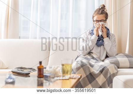 Ill Teen With Runny Nose Sitting On A Sofa At Home And Sniffling Because Of Cold And Fever. She Has