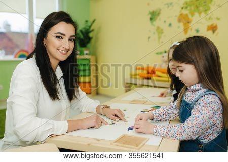 Teacher Learn Children In Preschool Classroom. Female Teacher In Kindergarden