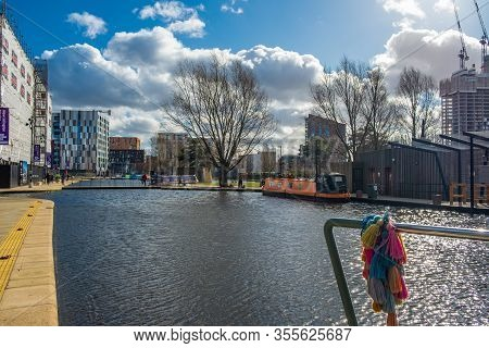 Manchester, United Kingdom - March 1, 2020: View Of People Walking And Boats Moored In A Canal In Ne