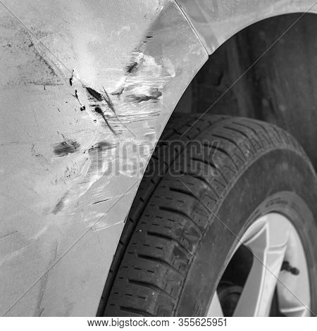 Generic Car With Scratched Paint And Dented Body In Crash Accident Or Parking Lot. Close-up.
