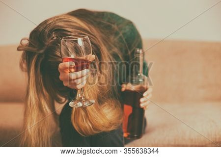 Depressed Woman Drinking Alcohol While Sitting Alone At Sofa